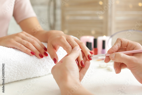 Fotografie, Tablou Woman getting professional manicure in beauty salon, closeup