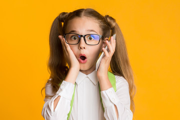 Surprised School Girl Holding Cellphone To Ear On Yellow Background