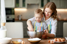 Happy Family In Kitchen. Mother And Child Preparing Dough, Bake Cookies.