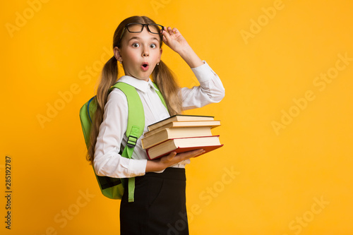 Shocked Primary School Girl Holding Stack Of Books, Yellow Background