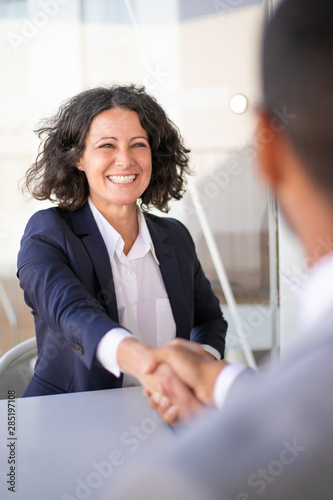 Happy successful business colleagues meeting outside and closing deal. Joyful business woman and man sitting at table, talking and shaking hands. Closing deal concept