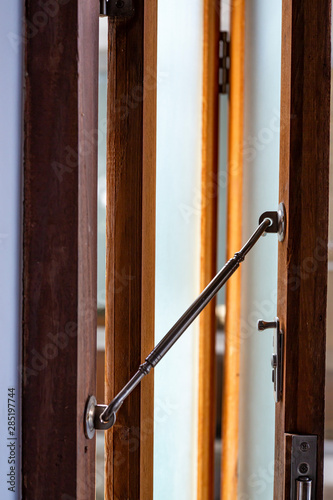 Photo Aluminium Latch  is connected to ajar frosted Glass and wooden door frame, Close