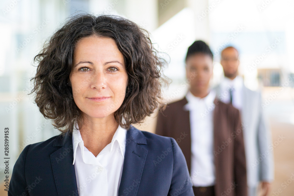 Fototapeta Successful female leader posing with her team in blurred background. Middle aged businesswoman smiling at camera, her two colleagues standing behind her. Successful team leader concept
