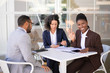 Happy African American business woman waving hello, while her colleagues discussing work issues. Multiethnic business man and women sitting in outdoor. Work break concept