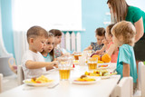 Kids have a dinner in kindergarten. Little boys and girls from the group of children sitting at table with lunch and eat appetizing. Children with caregiver in day care centre. Childs have healthy