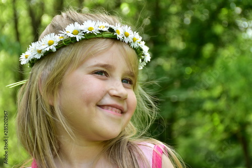 Valokuvatapetti portrait of a little girl with a wreath of daisies on her head,