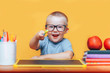 Little boy painting and doing homeworks on his desk having an idea, inspiration concept. back to school on yellow background
