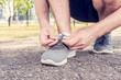 Athlete runner tying shoelaces, close up, cropped image, toned