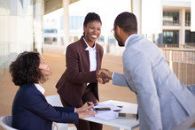 Happy Sales Agent Welcoming Customer In Outdoor Cafe. Business Man And Women Standing And Sitting At Table Outdoors, Shaking Hands And Smiling. Business Meeting Outside Concept