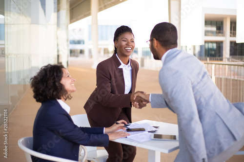 Fototapety, obrazy: Happy business partners meeting in outdoor cafe and greeting each other. Business man and women standing and sitting at table outdoors, shaking hands, talking and smiling. Partners meeting concept