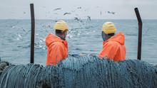 Crew Of Fishermen Work On Commercial Fishing Ship That Pulls Trawl Net.