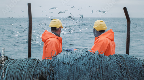 Fotografia Crew of Fishermen Work on Commercial Fishing Ship that Pulls Trawl Net