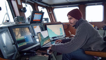 Captain Of Commercial Fishing Ship Surrounded By Monitors And Screens Working With Sea Maps In His Cabin.