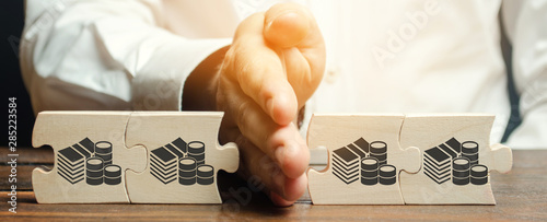 Businessman separates the wooden puzzle with a picture of money Tableau sur Toile