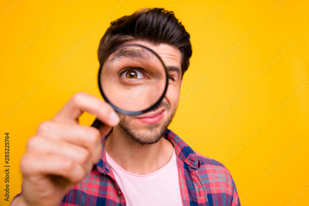 Fototapeta Photo of amazed man trying to see microorganisms with loupe but he evidently cannot manage to do it while isolated with yellow background