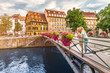 Leinwanddruck Bild - Two young happy girl friends standing on a bridge in Strasbourg while travelling in Petit France region. Tourism and friendship concept