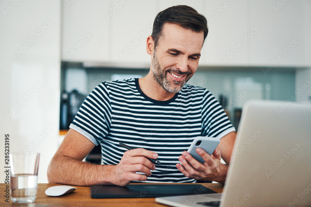 Fototapeta Happy web designer looking at smartphone while taking break from working in home office