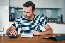 Smiling Man Managing Home Budget With Calculator And Notebook While Sitting At Dining Table