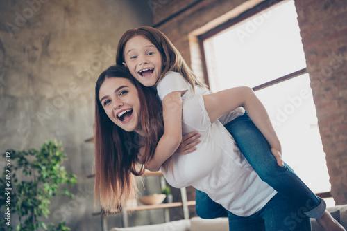 Fototapeta Portrait of cheerful lovely mommy kid laughing piggybacking wearing white t-shirt denim jeans in big house indoors obraz