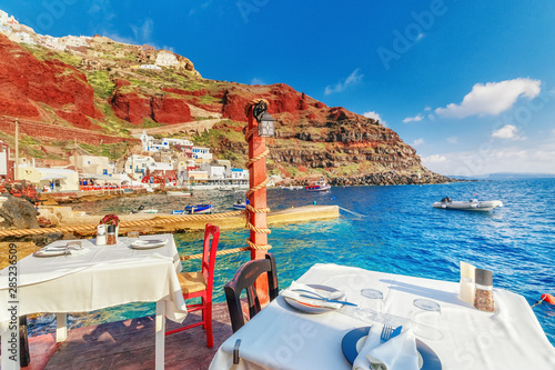 Foto auf Gartenposter Santorini Greece, Santorini. Panoramic sea view restaurant on Santoini in Greece, in Oia village. Restaurant with served table in seafront of Aegean sea on Santorini Cyclades island.