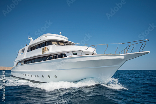 Luxury motor yacht sailing out on tropcial sea