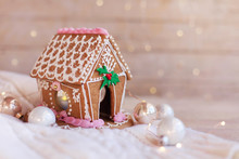 Gingerbread House, Christmas Decorations On Wooden Background With Glares. Homemade Sweets Is Decorated With Holly, New Year Lights, Garland And Cute White And Pink Ornaments.
