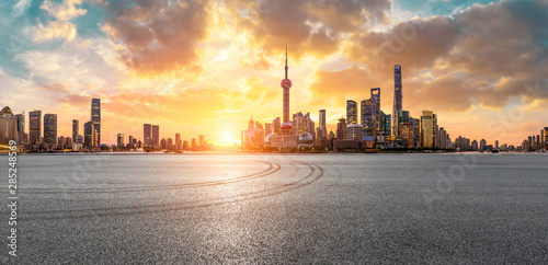 Foto  Shanghai skyline and modern buildings with empty race track at sunrise,panoramic view
