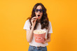 canvas print picture - Shocked young woman posing isolated over yellow wall background eat popcorn watch film.