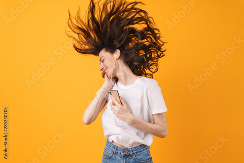 Vászonkép  Emotional smiling young woman posing isolated over yellow wall background listening music with earphones dancing using phone