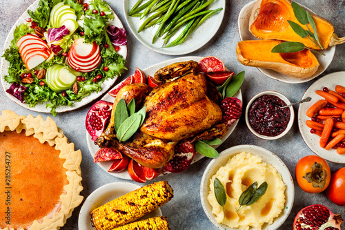 Photo  Thanksgiving dinner table with roasted whole chicken or turkey, green beans, mashed potatoes, cranberry sauce and grilled autumn vegetables