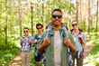 travel, tourism, hike and people concept - indian man in sunglasses and group of friends with backpacks in forest