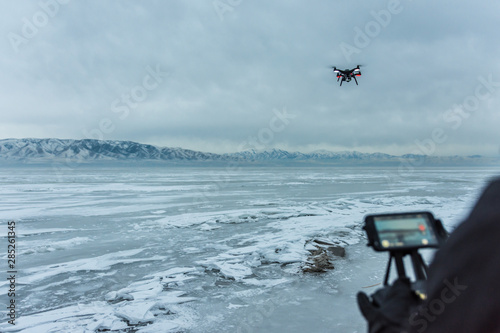 Valokuvatapetti Man flies black drone helicopter over frozen lake