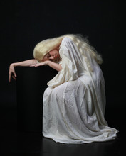 Ghostly  Portrait Of A Woman With Long Blonde Hair Wearing A White Robe. Posing Against A Black Studio Background.