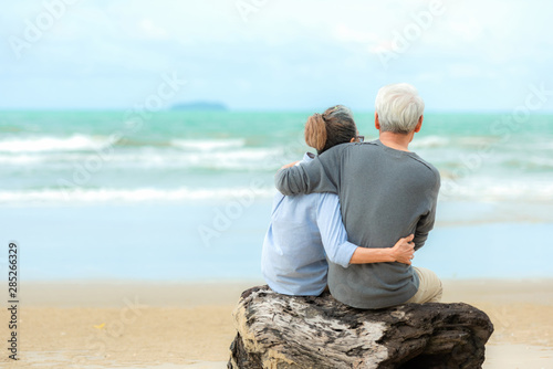 Foto  Asian Lifestyle senior couple hug and sitting on the beach happy in love romantic and relax time