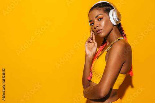 Obraz Image of athletic african american woman wearing afro braids listening to music with headphones - fototapety do salonu