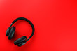 Leinwanddruck Bild - Wireless black headphones on a red background. View from above. In-ear headphones for playing games and listening to music tracks