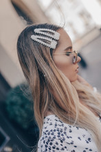 Close Up Portrait Of A Young Blonde Woman With Natural Hairstyle. Her Tresses Are Adorned With Pearl Hair Clips.
