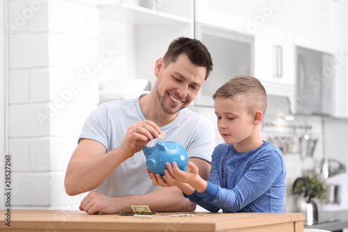 Foto Family with piggy bank and money at home