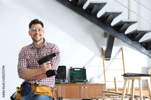 Fotografía  Handsome working man with electric screwdriver indoors, space for text