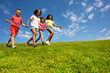 canvas print picture - Group of kids run on the grass field holding hands