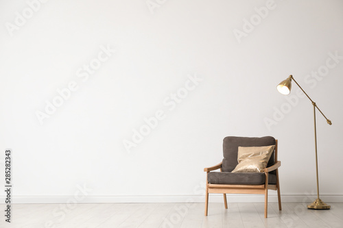 Stylish living room interior with wooden armchair and floor lamp near white wall Wallpaper Mural