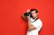 Leinwanddruck Bild - Young professional photographer taking picture on red background. Space for text