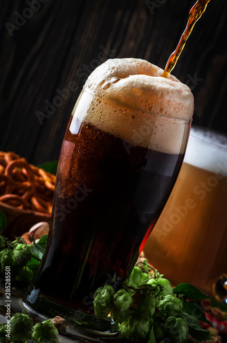Canvas Print Dark english beer, ale or stout is poured into glass, dark bar counter, space fo