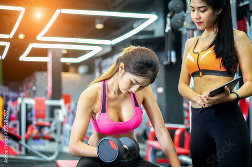 Spoed Foto op Canvas Fitness The Trainer check post with Young fitness woman execute exercise with dumbbell in gym, horizontal photo.