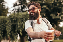 Bearded Adult Man Riding Electric Scooter And Drinking Coffee