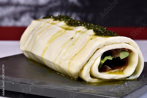 Obraz na plátně  basil pesto mozzarella roulade served on stone