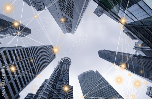 Digital network connection lines of high-rise office buildings, skyscrapers, architectures in financial district. Smart urban city for business and technology concept background in Downtown Singapore.
