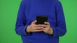 A young boy works on a smartphone - front closeup - green screen studio