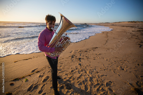 Man musician with a tuba playing on the ocean beach. - 285322355