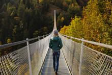 Woman Walking Along A Suspension Bridge